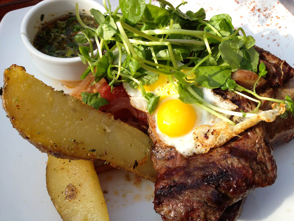 Patagonian grill with fried quail eggs and native potatoes