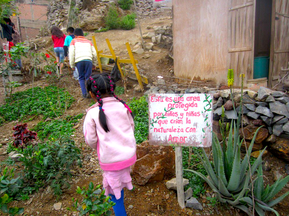 "The board reads: ""this garden is protected by boys and girls that create nature with love"""