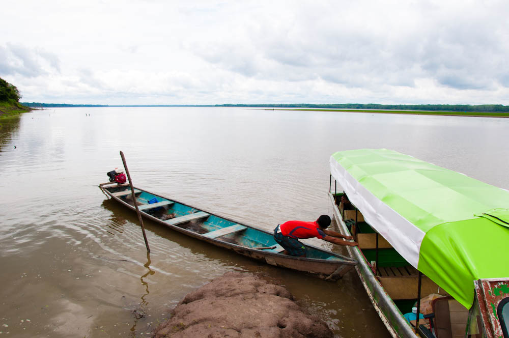 Transfering from the speed boat into a canoe, where the Amazon river meets it's subsidiary, the Tapira river.