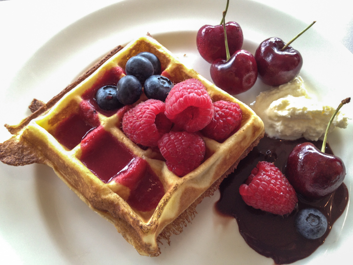 Dessert: waffle with fresh raspberries, blackberries and cherries, dark chocolate sauce and cream